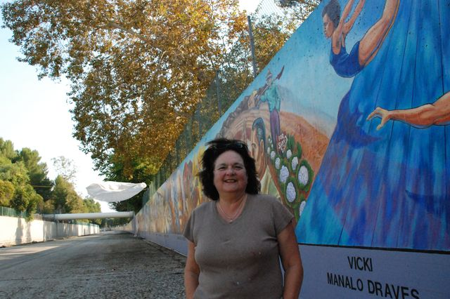 "Judy Baca, professor of Chicana and Chicano studies at UCLA, standing in front of her mural ""The Great Wall of Los Angeles"""