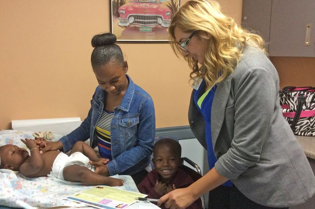 Sandra Contreras, a parent coach, meets with Kioki Johnson and her family during a well-child checkup at Wee Care Associates.