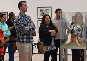 Teachers take a guided tour of a soccer exhibit at the Los Angeles County Museum of Art