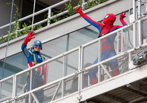 Superhero window washers on a cleaning platform