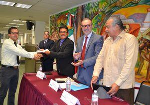 Lopez-Flores receives a check from associate professor of sociology Rubén Hernández-León