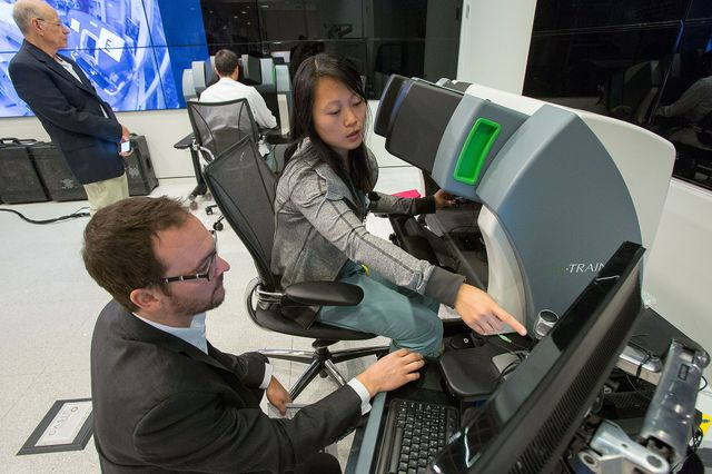 Instructors monitor trainees in robotic surgery.