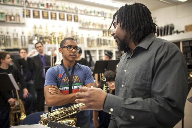 Monk Institute alto sax player David Otis talks to a student musician at North Hollywood High School about the finer points of jazz