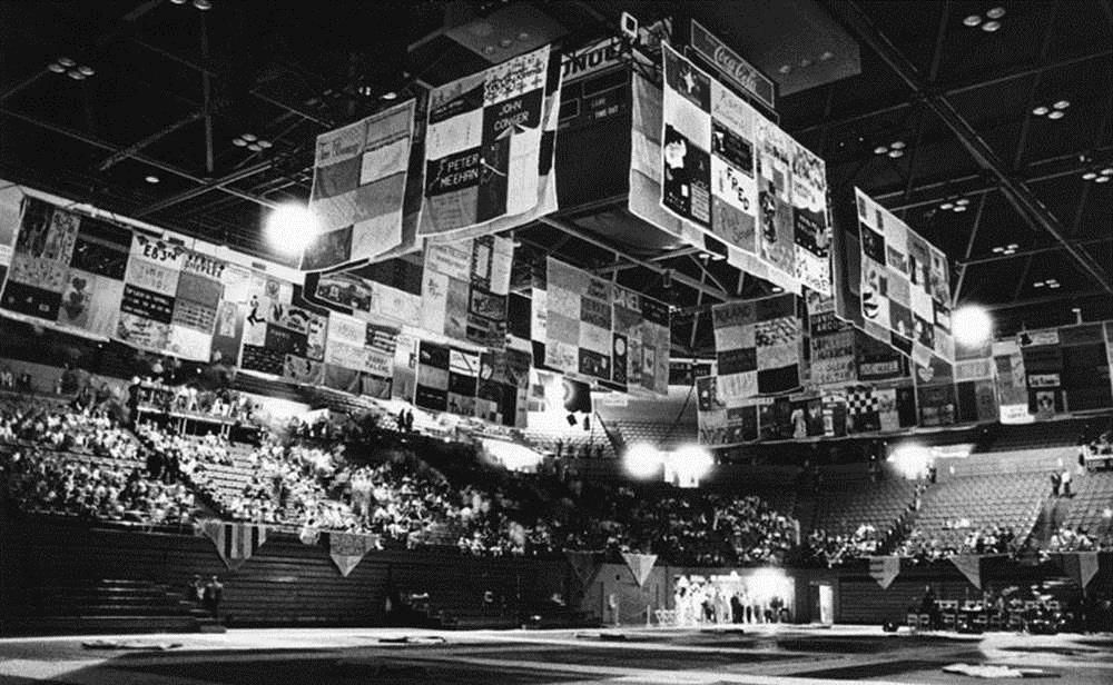 Panels of the seven-ton patchwork quilt, which memorializes those who have died of AIDS, hang from the ceiling and have been placed on the floor inside Pauley Pavilion on the UCLA campus in preparation for a fund-raising event. At the time this photograph was taken in April 1988, more than 800 volunteers had worked on the Names Project quilt.