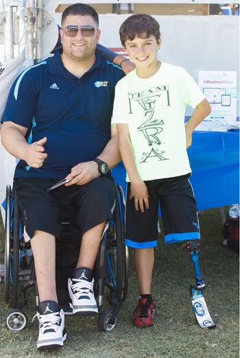 UCLA adaptive recreation coordinator, Michael Garafola, in his wheelchair, with adaptive athlete Ezra Frech, on his running prosthetic, at an event in October