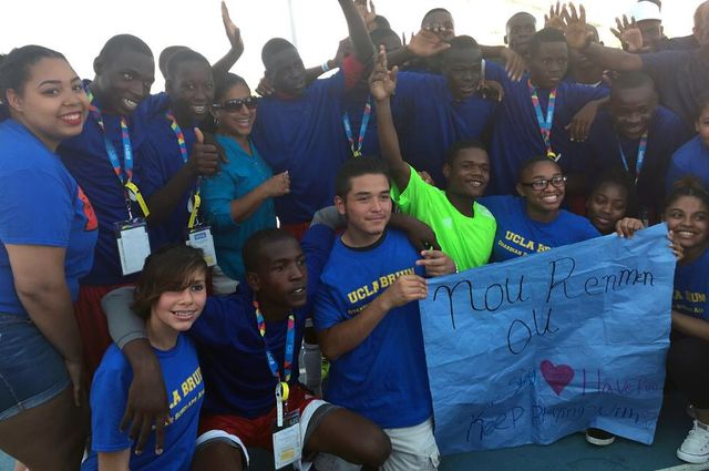 "Team Haiti and First Star UCLA Bruin Guardian Scholars Academy students celebrating and holding a sign made by the students that says, ""We Love You"" in Creole on July 26."