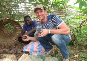 Grant Guess and the school's farmer, Thomas Bodzrenou, hold some of the giant land snails that will be bred and raised at the school and then sold to local markets and restaurants.