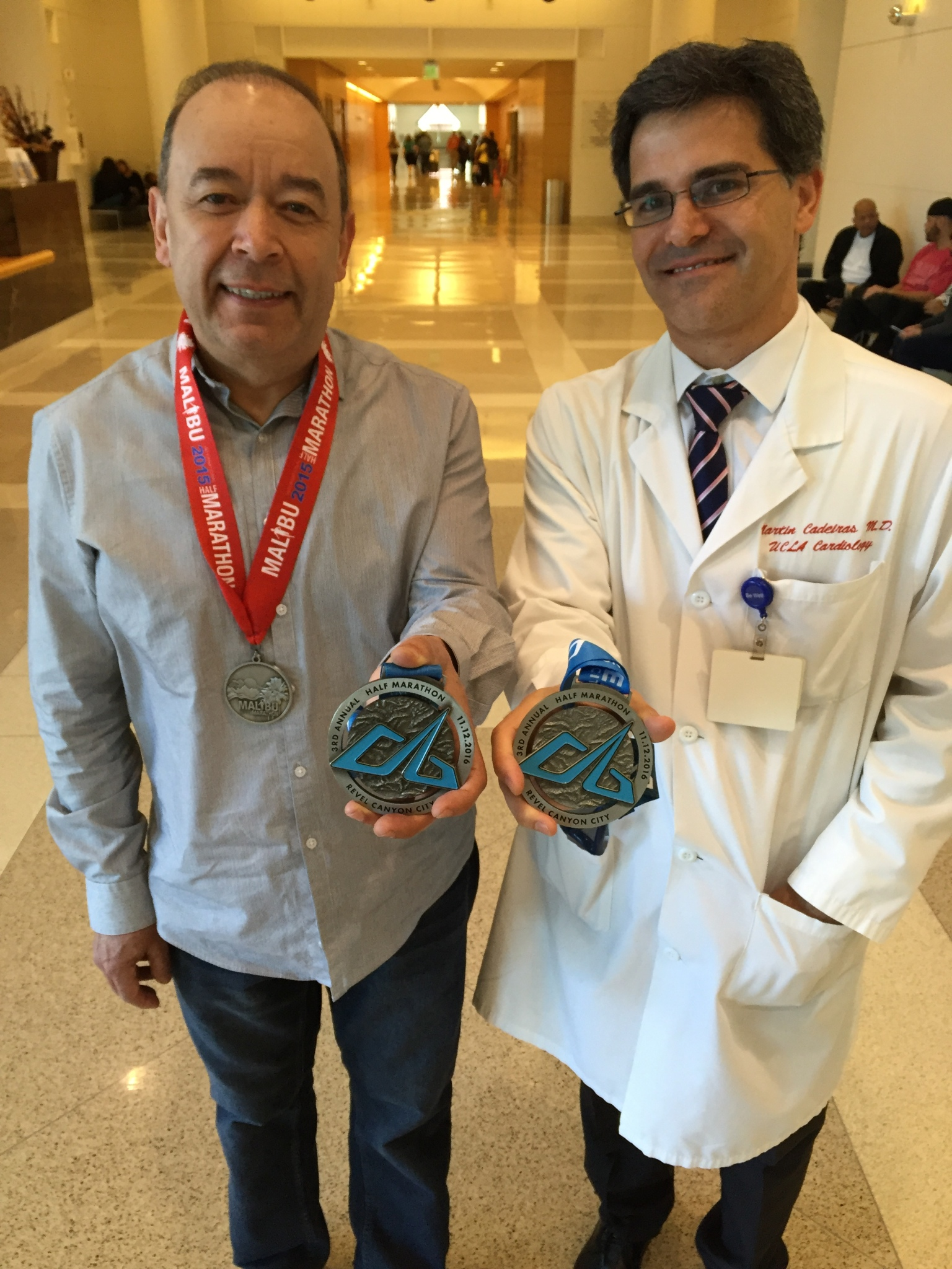 Tony Flores, at left, and Dr. Martin Cadeiras show off their half-marathon medals at Ronald Reagan UCLA Medical Center, where Flores had his heart transplant surgery.