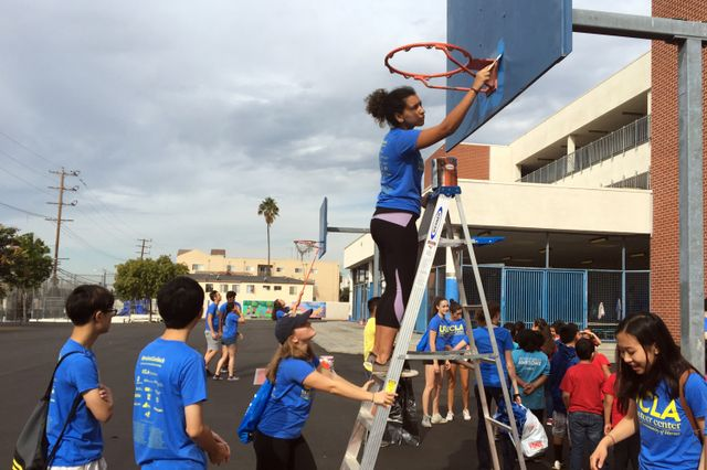 UCLA students paint the backboard at Hoover Elementary School.