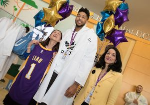 UCLA neurosurgeon Dr. Linda Liau looks up at Laker forward Brandon Ingram. Standing next to him is Johnese Spisso, president of UCLA Health and CEO of the UCLA Hospital System.