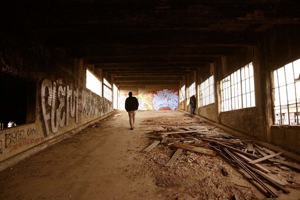 A man walks through an abandoned factory in the Midwest