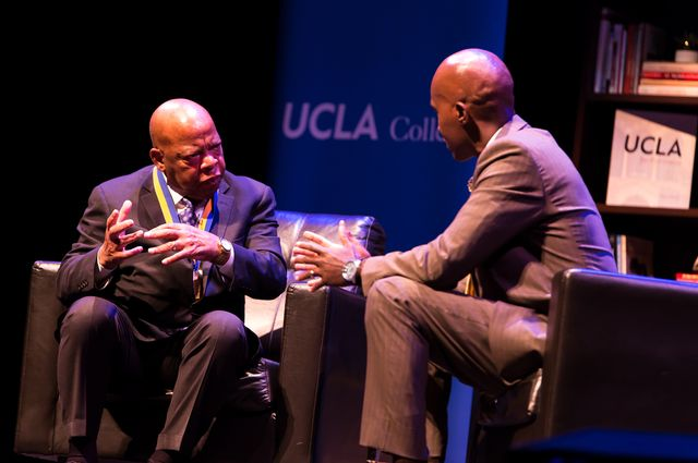 John Lewis talks on a stage with Tyrone Howard