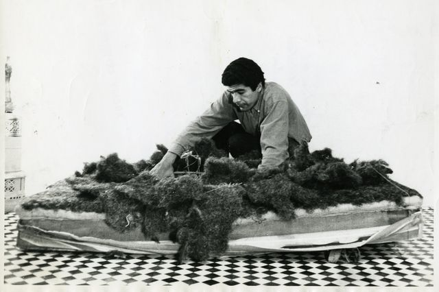 Black and white photo of Raphael Montañez Ortiz deconstructing a mattress as part of his art.