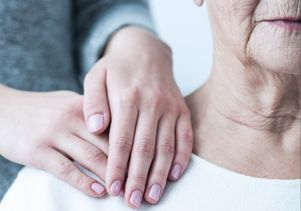 Hands on shoulder of elderly woman