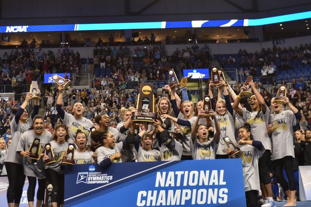 UCLA gymnastics with NCAA trophy
