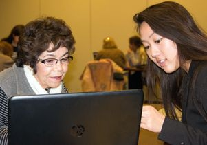 UCLA student Lauren Bui helps a woman learn how to better use a laptop.