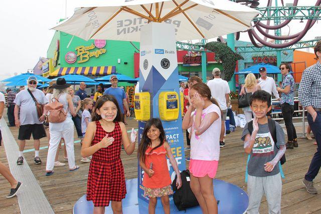 Kids use sun safety kiosk