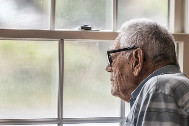 Senior man looking out window