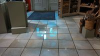 Water is reflected from the ceiling lights on the floor of the gift shop in the Maxwell Museum of Anthropology