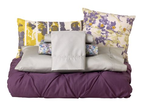 Oblong Yellow and Gray Floral Toss Pillow, Gray Floral Toss Pillow, Queen Performance Sheet Set in Geo Gray, Queen Performance Sheet Set in Purple Floral and Queen Pintuck Comforter in Purple