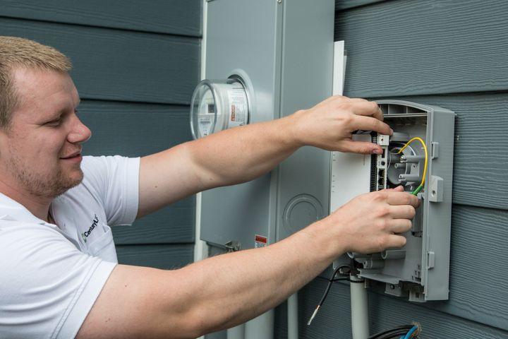 Technician installs fiber to the premises (FTTP)