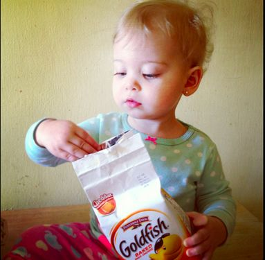 It's snacktime for this sweet little Goldfish fan