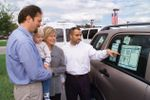 family buying car looks at mileage sticker