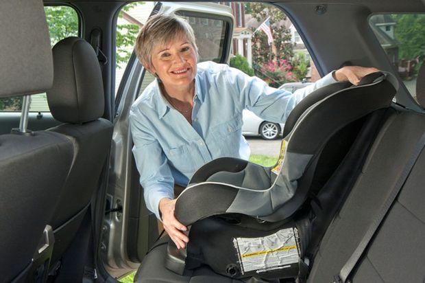 Woman grandma puts carseat in car