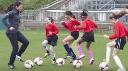 Mia Hamm plays soccer with kids