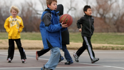 Boy holding basketball with others in background