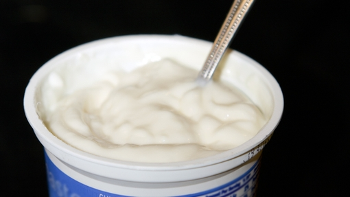 Yogurt LowFat plain in cup with spoon verticle